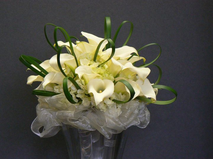 White calla lilies, hydrangeas, and loops of lily grass make up this simple, yet elegant bride's...