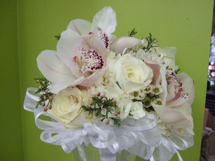 A bouquet of white roses, cymbidium orchids, and waxflower.