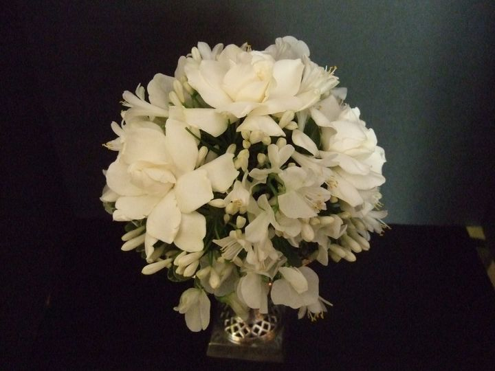 This fragrant bouquet features gardenias, roses, and agapanthus blooms.