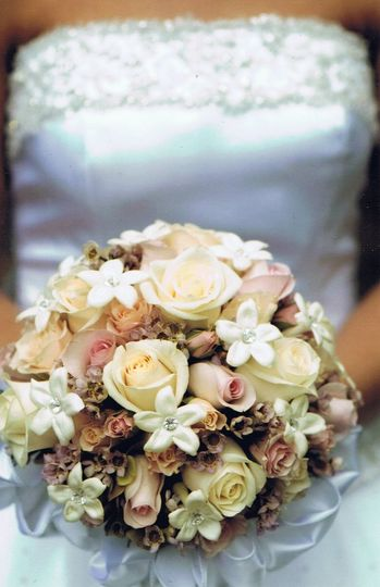 This timeless bouquet features Vendela, Champagne, and Porcelina roses with wax flower, and a bridal...