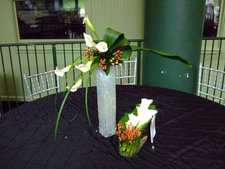A couple different styles of centerpieces, both using calla lilies and red hypericum berries.  The...