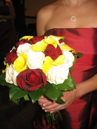 Bridal bouquet made of dark red bacara and ivory roses, mixed with yellow miniature calla lilies