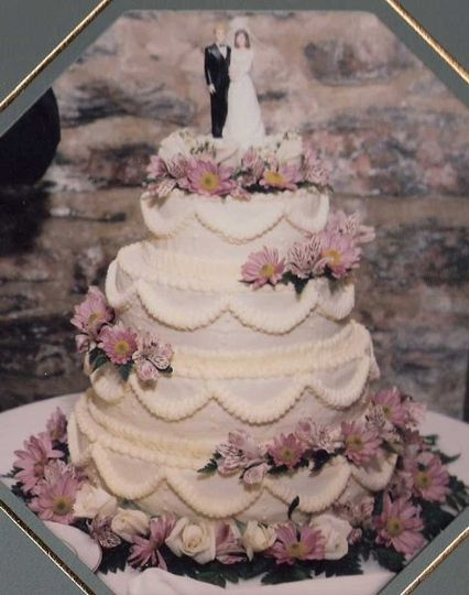 Wedding cake trimmed with ivory sweetheart roses, pink alstomeria, and lavendar/ orchid daisy mums