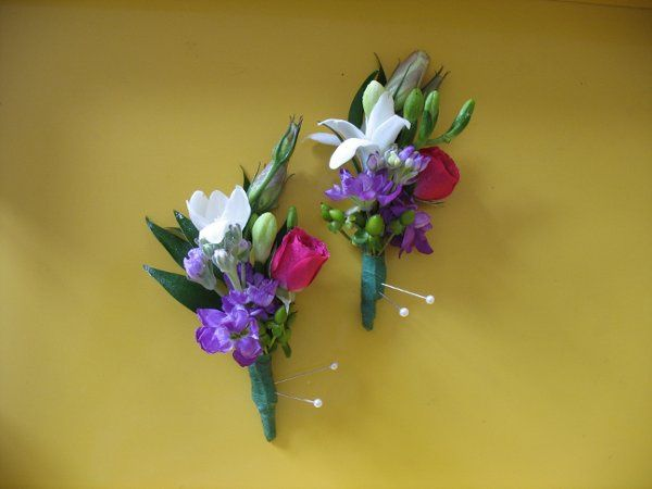 Boutonniere made with white freesia, blue/ purple delphinium, and hot pink spray rose