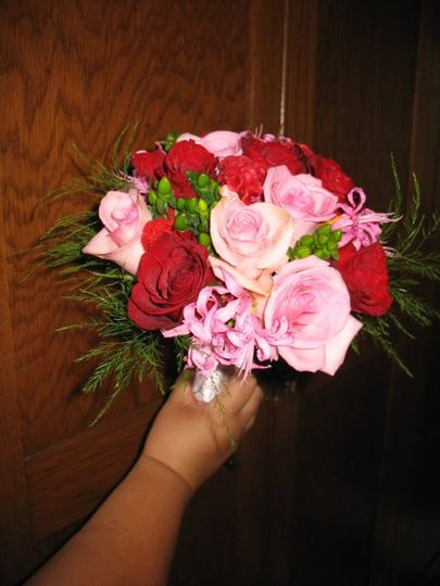 Bridal bouquet of pink and red roses, pink nerine lilies, and green hypericum berries, trimmed with...