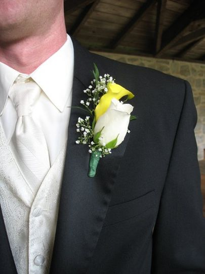 Boutonniere of ivory rose with yello miniature calla lily and babies breath