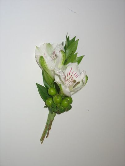 Boutonniere of white alstromeria and green hypericum berries