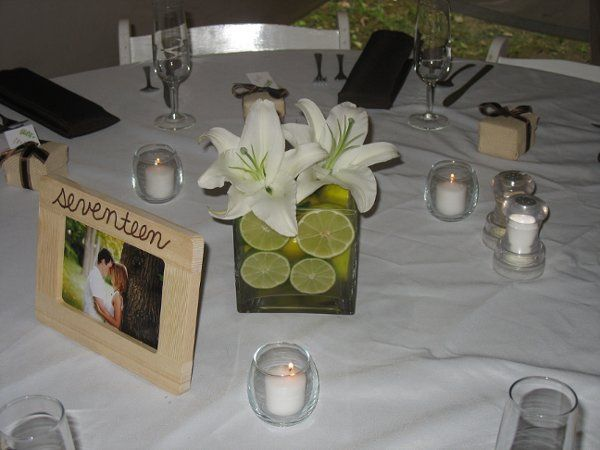 Square glass centerpiece filled with lime slices and topped with white lilies