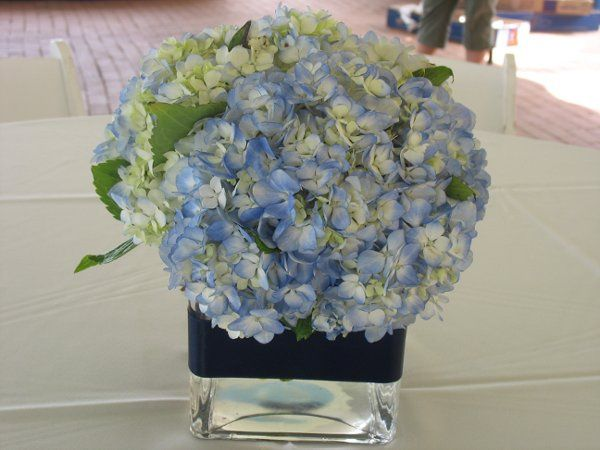 Square glass centerpiece, trimmed with navy ribbon, filled with blue hydrangea