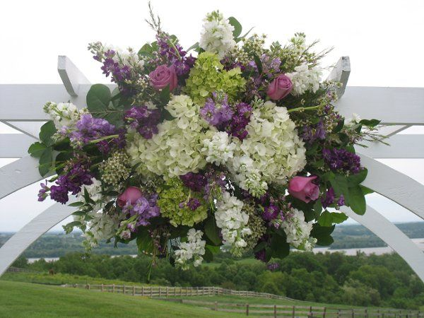 Ceremony arch swag made with mix of white and purple stock, white and green hydrangea, lavendar...