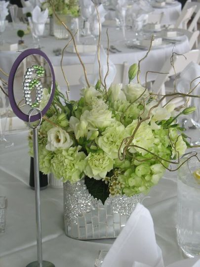 Centerpiece of green/ white hydrangea, green carnations, white lissianthus and white freesia....