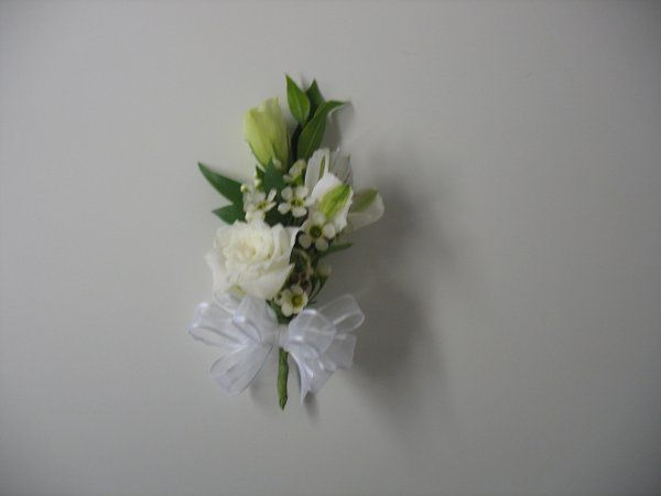 Corsage made with white rose, white lissianthus, white alstromeria, wax flower