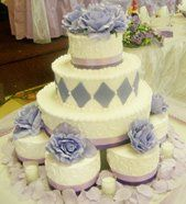 Buttercream tier cake with six individual cakes.  Accent with purple fondant diamonds and satin...