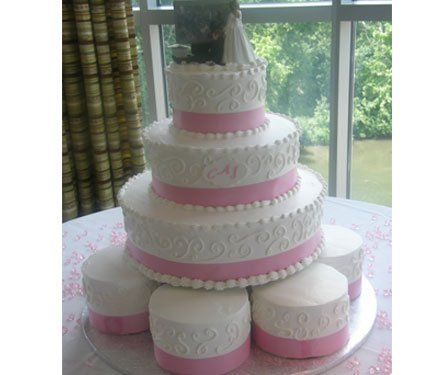 Buttercream tier cake with six individual cakes.  Accent with pink ribbon.