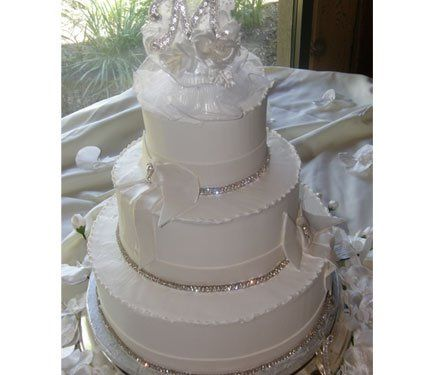 Tiered buttercream cake with fondant ribbon and bow.  Bling ribbon accent cake!