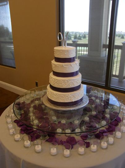 Tiered cake with buttercream icing and purple ribbon to accent.  Silk petals and votive candles...