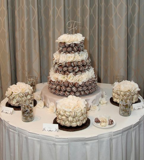 3 tiered cake bite wedding cake with individual satellite cakes.  Silk flowers added to cakes.