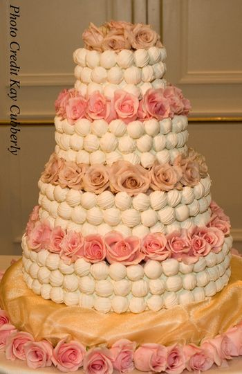 Cake bite wedding cake with fresh roses between tiers.
