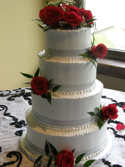 Tiered buttercream cake with fresh roses and ribbon.