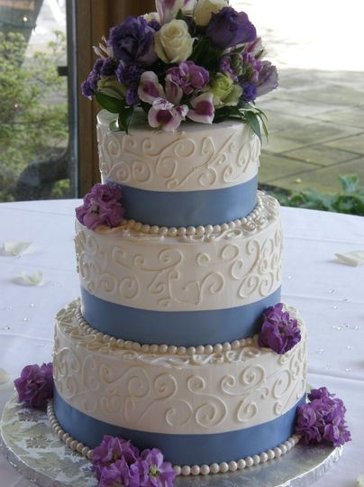 Tiered buttercream cake with satin ribbon and fondant pearls!  Fresh flowers are used for the...