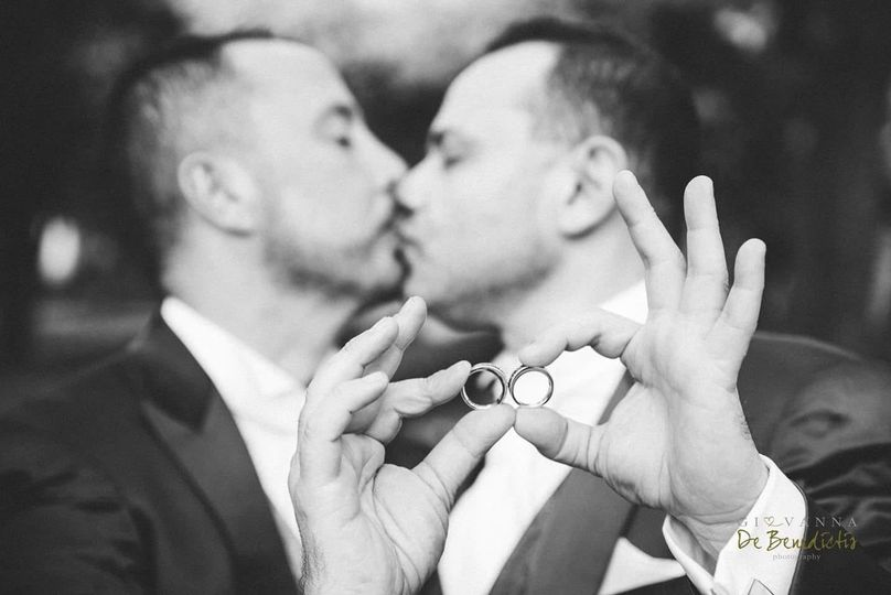 Holding their wedding bands as they kiss