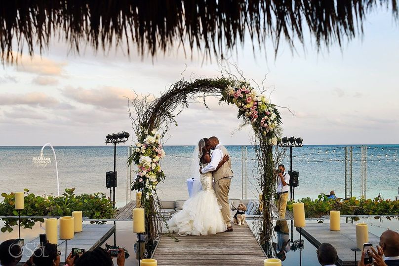 Couple kissing under the wedding arch