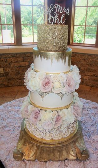 Flower decorated wedding cake with golden sparkles