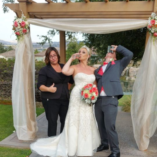 Playful shot of the newlyweds and the officiant