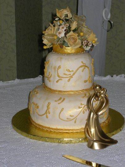 A small but elegant cake for a Destination Wedding.  Fondant covered with piped scrollwork and a...