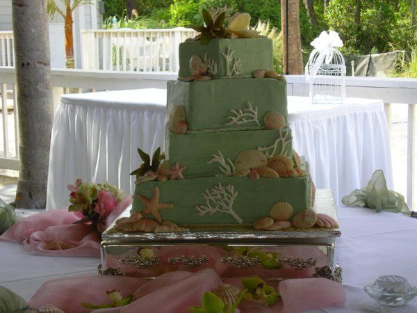 Butter cream covers this cake with a seaside theme, designed by the groom.  The flowers are handmade...