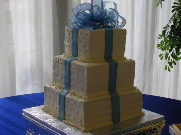 Butter cream covers this stack of boxes made of French vanilla cake.  Fondant ribbons adorn the...