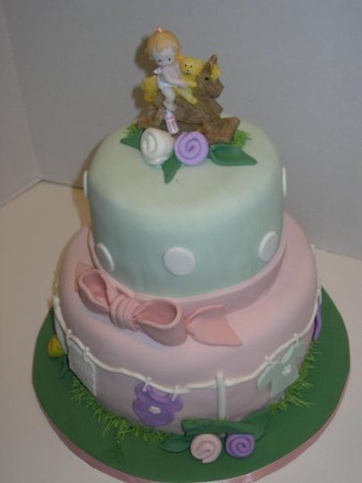 A baby shower cake covered in fondant with a clothesline of baby things blowing in the breeze. A...