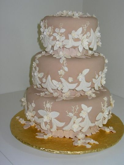 This fondant covered cake is almost completely covered with gumpaste flowers and piping as well as...
