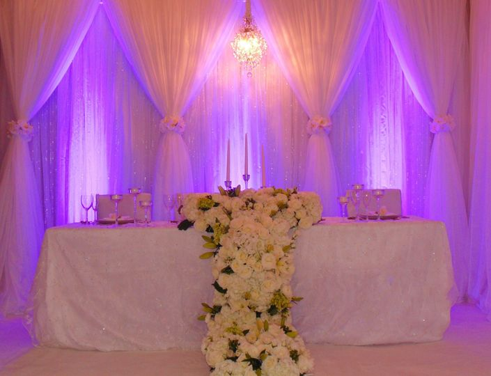 Large floral cascade. White chiffon draping with accent uplighting.