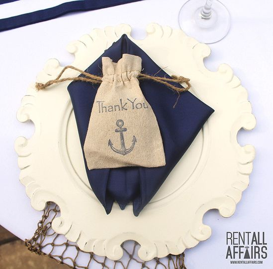 Place setting with charger plate, navy napkin and a nautical thank you gift bag.