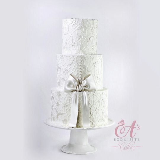 All white wedding cake with bow