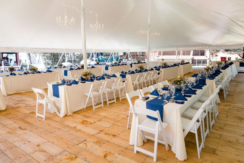 "Banquet tables with linens and padded garden chairs, spell out ""laid back"" for dinner"