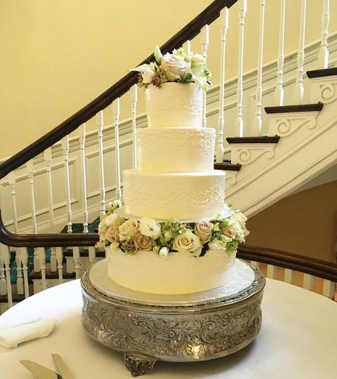 4-tier wedding cake with floral topper