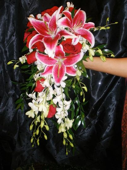 stargazer lilies, red roses, white dendrobiums arranged in a cascade bouquet