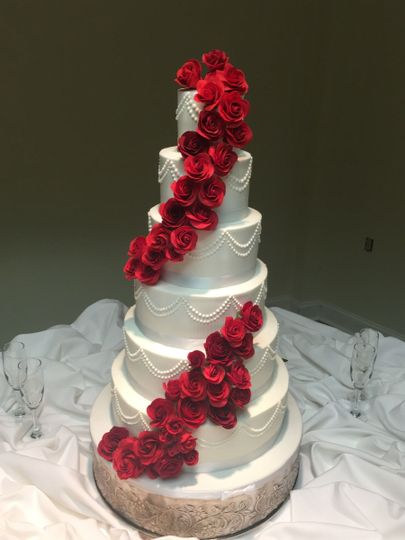 Red roses beautifully cascading down the cake with piped pearl garlands.