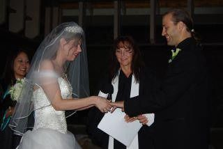 Bride putting a ring on her groom