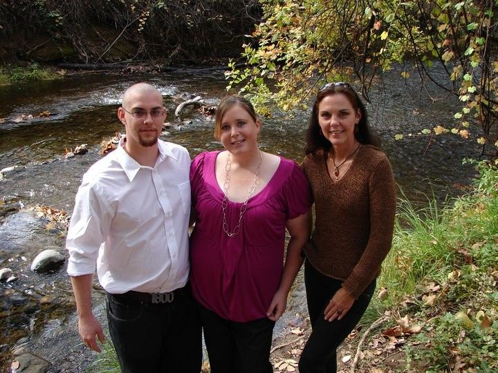 Newlyweds and officiant by the river
