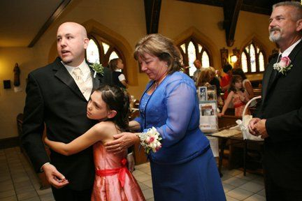 A groom is held by his daughter as he walks toward the bride during the ceremony as his parent look...