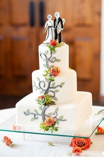 White wedding cake with the newlyweds' figurines on top