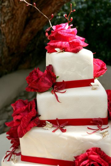 Wedding cake with red flowers and ribbons