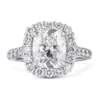 Engagement Ring in 18k white gold with a cushion cut center and a pave set shank. Color and Clarity:...