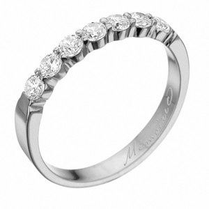 Round brilliant cut diamonds go 1/3 of the way around this wedding band, in 18k white gold or...