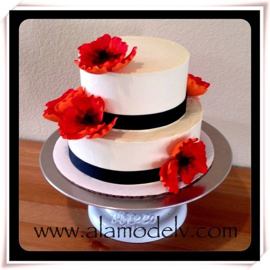 A two tier velvet a la mode cake with vanilla frosting. Complete with red poppies & black accents....