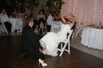 Groom taking off the garter from his lovely bride.