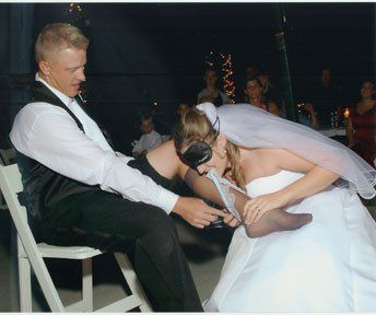 Reversal. Bride putting the garter on her husband. Not so easy.